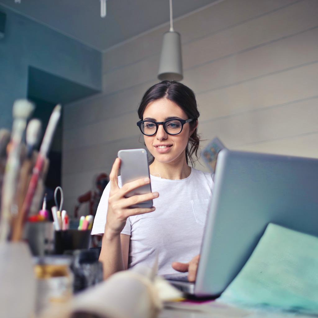 Een jonge onderneemster kijkt lachend op haar smartphone