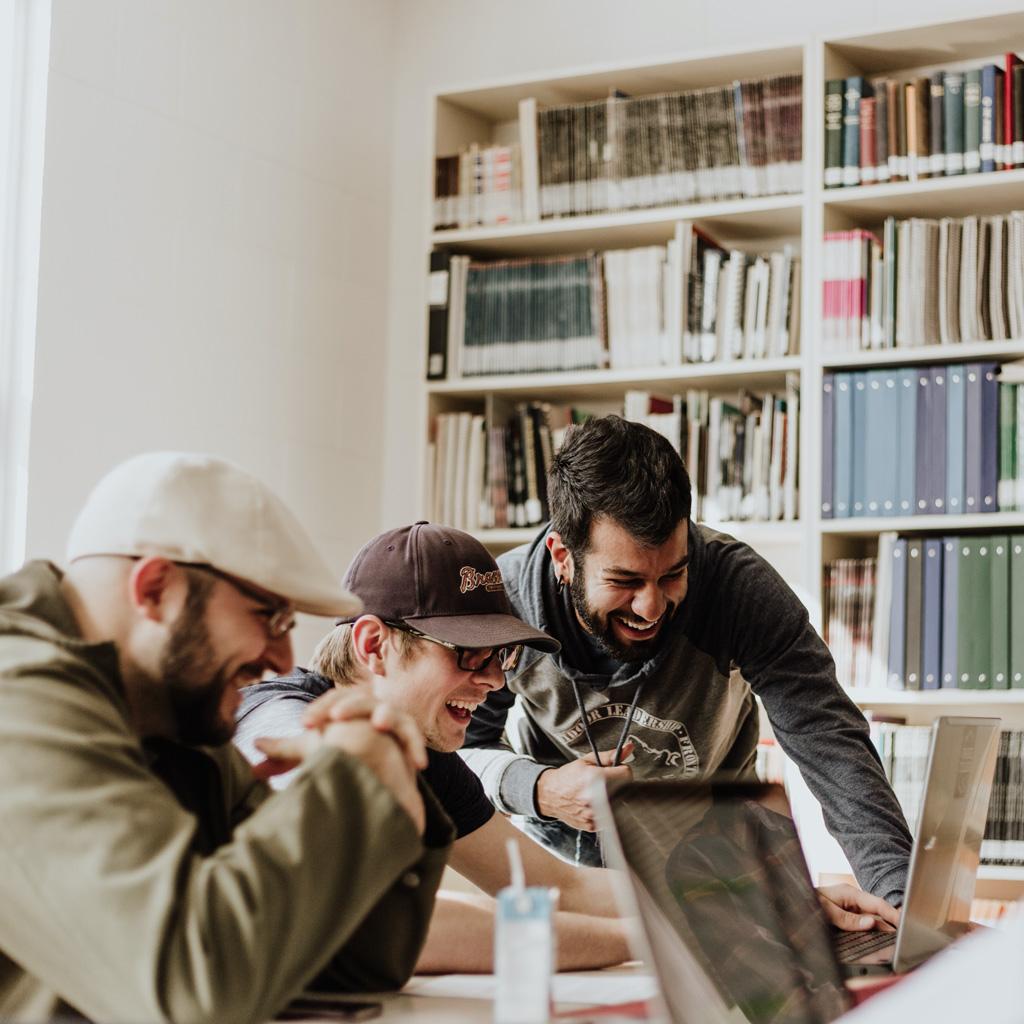 Trois partenaires d'un établissement Horeca regardant un écran d'ordinateur tout en rigolant